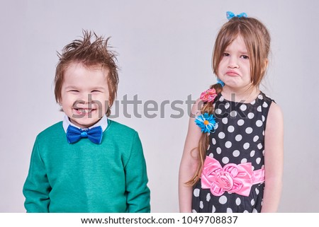 A handsome little boy, wearing a blue bow tie and a green sweater, laughs at a crying girl #1049708837