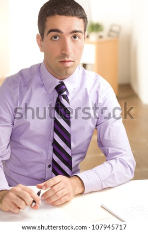 A handsome man at work with a surprised look on his face writing on paper wearing purple shirt and tie