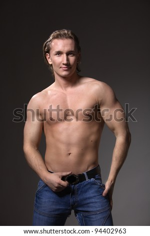 a handsome man athletic, male model posing in the studio, showing the positive and the beauty of the figure