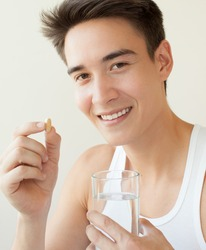 A handsome man holding up vitamin pill