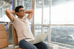 A handsome man in a casual style is worry free expression looking far to the copy space, Optimistic man put laptop over his leg while open his arm to relax from stress work. Work anywhere concept.