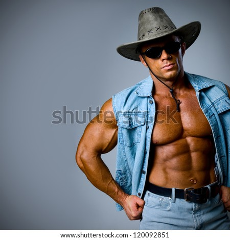 A handsome man in a cowboy hat on a gray background