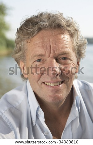 A handsome man in his fifties relaxing near by a sea