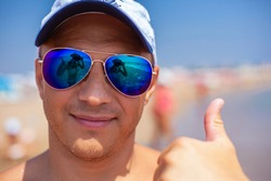 A handsome man in sunglasses gives a close-up thumbs-up. The reflection in the sunglasses.