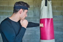 A handsome man punching a boxing bag