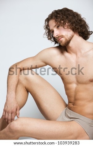 a handsome man sitting bare-chested poses in the studio