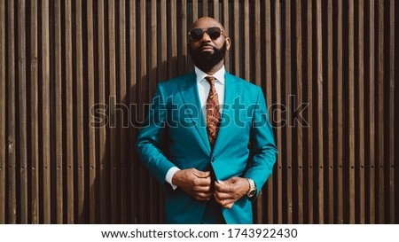 A handsome mature bald bearded African man in a sunglasses and a fashionable blue or teal costume with a tie is standing in front of a wall made of striped wooden timbers and fastening a suit button Foto stock ©