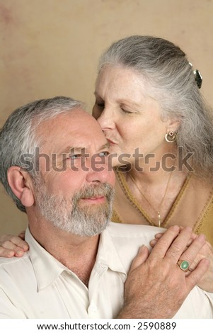A handsome mature man getting a kiss from his beautiful wife.