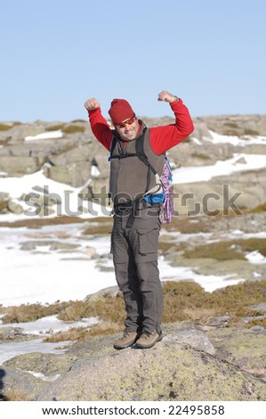 A handsome middle age hispanic latin man in a top of a  in mountain hiking in winter