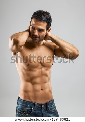 A handsome muscular man posing at a studio.