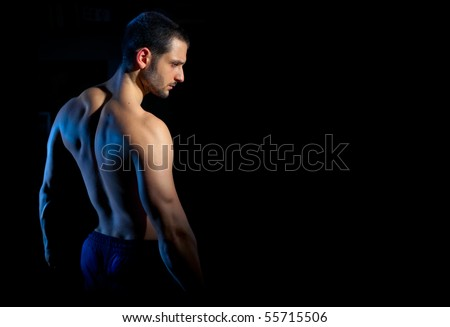 A handsome muscular man posing on a black background. Shallow depth of field with focus on model's face.