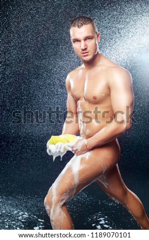 a handsome muscular  young man taking shower  with sponge and foam