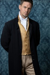 A handsome Regency gentleman wearing a gold waistcoat and black jacket and standing in a room with blue wallpaper and a wooden floor