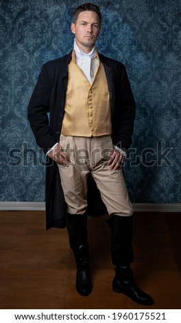 A handsome Regency gentleman wearing a gold waistcoat and black jacket and standing in a room with blue wallpaper and a wooden floor Foto stock ©