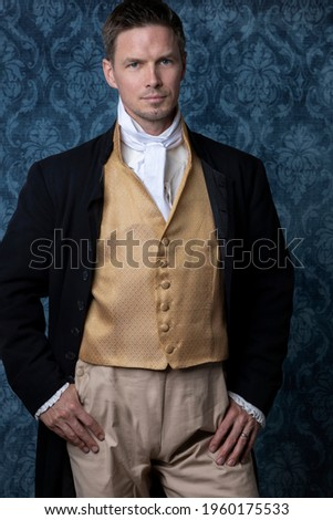 A handsome Regency gentleman wearing a gold waistcoat and black jacket and standing in a room with blue wallpaper and a wooden floor Stock photo ©