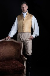 A handsome Regency gentleman wearing a linen shirt, gold waistcoat, breeches and leather boots and standing in a darkened room