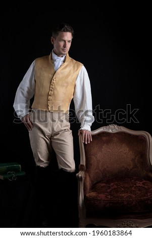 A handsome Regency gentleman wearing a linen shirt, gold waistcoat, breeches and leather boots and standing in a darkened room  Stockfoto ©