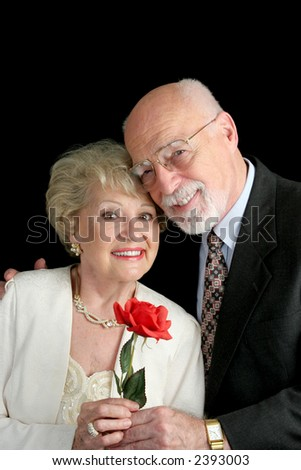 A handsome, romantic, senior couple holding a red rose, posing against a black background.