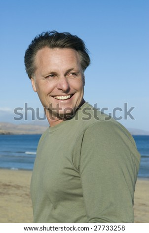a handsome smiling man on the beach.