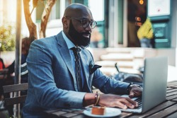A handsome stylish mature bald black man entrepreneur with a well-groomed beard, in spectacles, and a fashionable suit is using his laptop while sitting in a street cafe during the coffee break