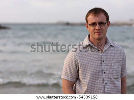 A handsome 35-year-old man in the background of the sea