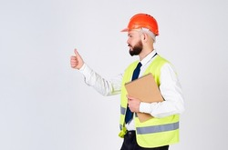 A handsome young architect with a beard, wearing a yellow reflective vest and a studio helmet, wearing a white shirt and tie, looks to the side and shows a like sign.