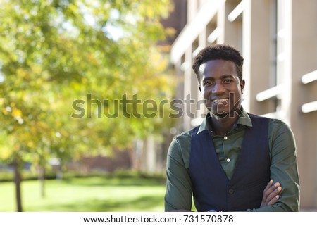 A handsome young black male student smiles standing on college campus