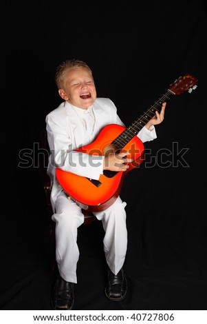 A Handsome Young Boy singing, in a White Suit and with Guitar