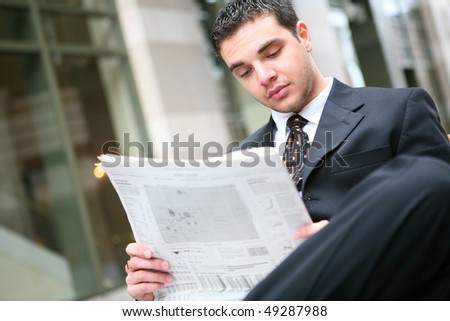 A handsome young business man reading the newspaper at office building