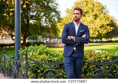 A handsome young businessman standing and waiting at the side of a park