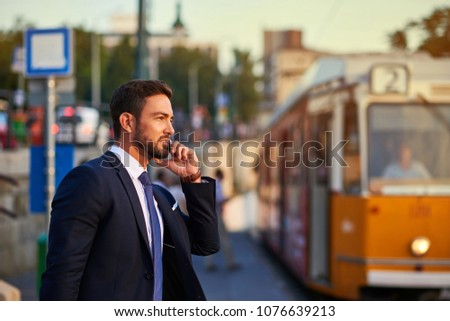 A handsome young businessman talking on his phone and waiting for the tram in the sunset