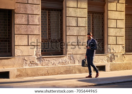 A handsome young businessman walking on the street in the sunset #705644965