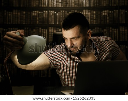 A handsome young guy with a beard is sitting at a table in a library. Hitchcock style picture of a bearded guy
