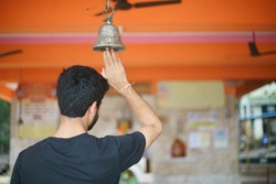 A handsome young Indian man is ringing a bell at a local Hindu temple in Mumbai, India.