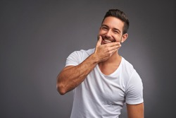 A handsome young man checking the skin on his face and smiling