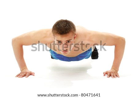 A handsome young man dressed in blue shirt making push-ups
