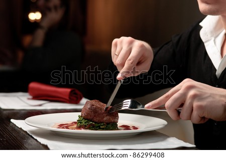 A handsome young man eating delicious meat cutlet with a knife and fork at a table elegantly served