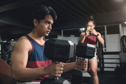 A handsome young man hypes himself up for a heavy lift, while a woman at the back records his feat with her cellphone for a vlog, social media post or story.