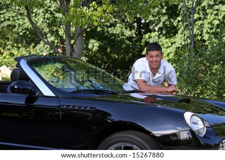 A handsome young man leaning on a luxury black convertible.