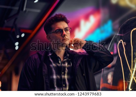 A handsome young man standing at night in the street. Illuminated signboards, neon, lights. #1243979683