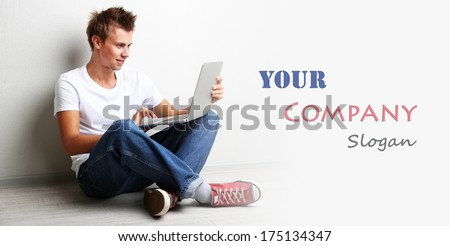 A handsome young man with laptop on grey background