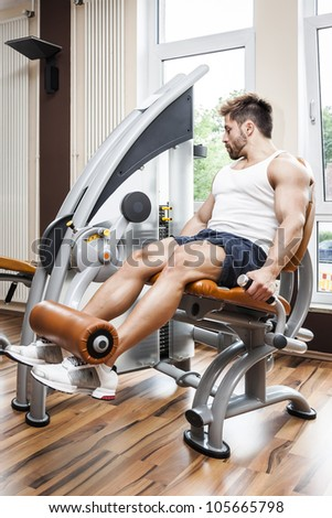 A handsome young muscular sports man doing leg press