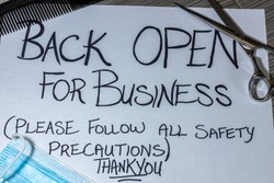 a handwritten sign letting the public know that this barber shop is back open after the restrictions from covid 19 have been lifted