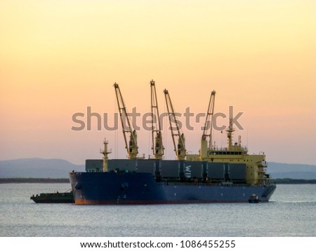 A handy-sized bulk carrier loads iron-ore from barges at Wyndham, in Western Australia, as the sun sets behind it.