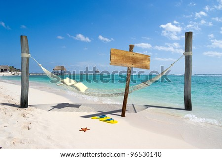 A hanging hammock, a wooden sign post , thongs and starfish on a beach resort