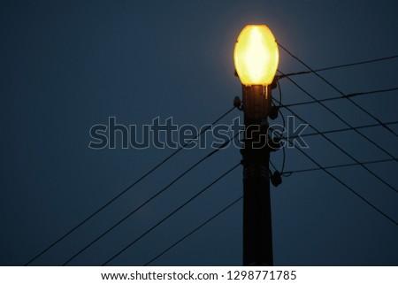 A hanging street lamp against a serene dark sky art #1298771785