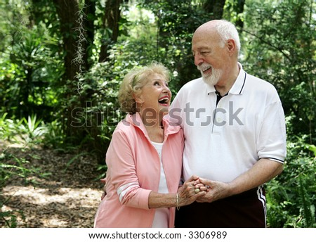 A happy, active senior couple laughing together on a walk through the park.  She's wearing a hearing aid.  Plenty of copy space.