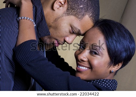 A happy african american couple smiling and embracing.  The man is looking at the woman and the woman is looking at the camera