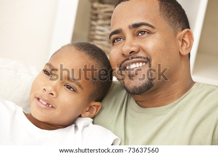 happy african american man and boy father and son family sitting