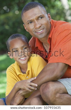 A happy African American man and boy, father and son, family together outside in summer sunshine